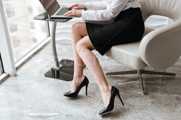 Cropped photo of young business woman using laptop. Stock photo © deandrobot