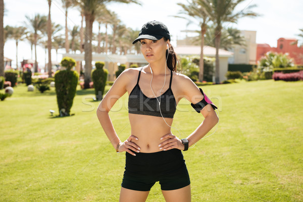 Sportswoman in cap with earphones and armband standing on lawn Stock photo © deandrobot