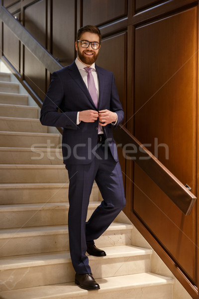 Happy young bearded businessman standing on ladder Stock photo © deandrobot