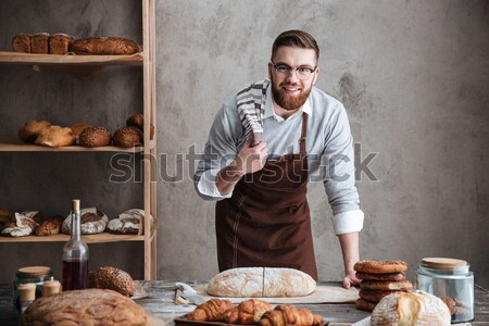 Cheerful loving couple bakers looking aside. Stock photo © deandrobot