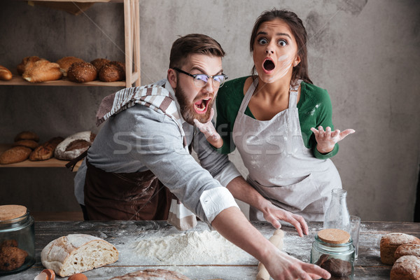 Shocked man and woman standing near table with flour Stock photo © deandrobot