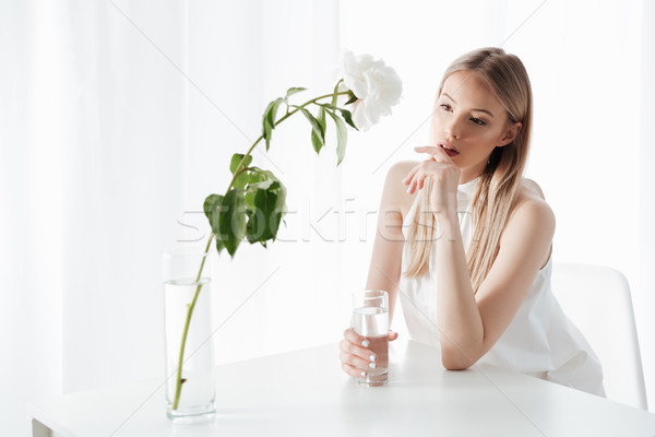 Concentrated blonde lad holding glass of water. Stock photo © deandrobot