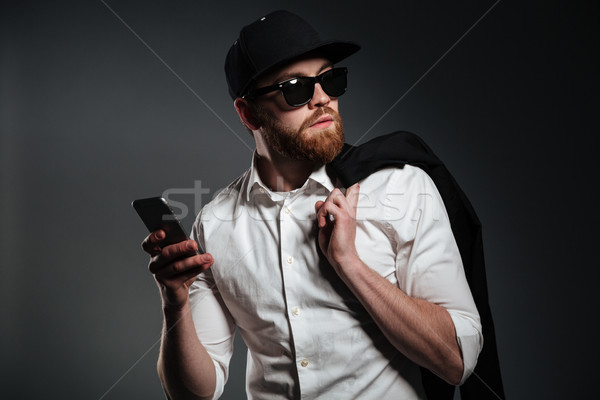 Man in sunglasses and shirt holding phone and looking away Stock photo © deandrobot