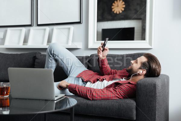 Feliz joven mentiras sofá escuchar música Foto stock © deandrobot