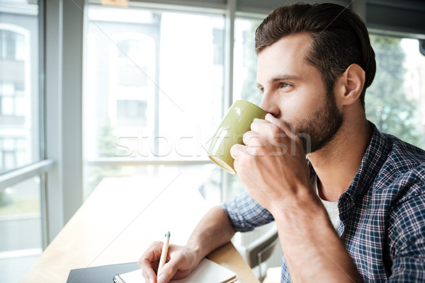 Handsome man in office coworking while writing notes drinking tea Stock photo © deandrobot