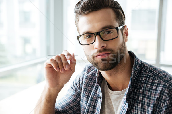 Handsome man wearing glasses sitting in office coworking Stock photo © deandrobot