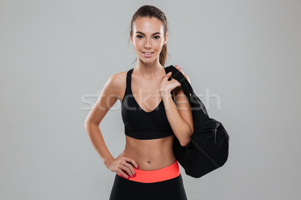 Smiling fitness woman with bag holding arm on hip Stock photo © deandrobot