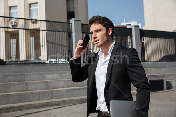 Stock photo: Serious young businessman walking outdoors talking by phone.