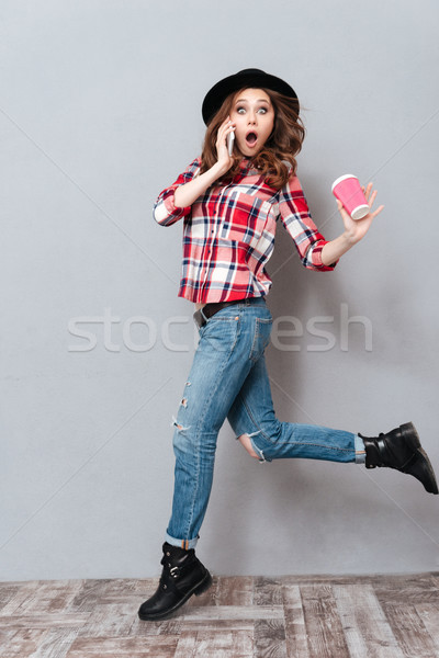 Portrait of a surprised pretty girl in plaid shirt talking Stock photo © deandrobot