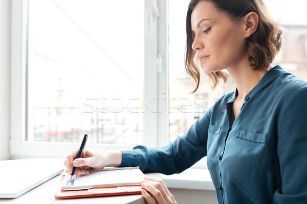 Widok z boku kobieta zauważa dziennik młoda kobieta Zdjęcia stock © deandrobot