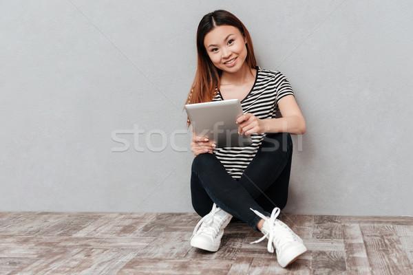 выстрел улыбающаяся женщина сидят полу таблетка молодые Сток-фото © deandrobot