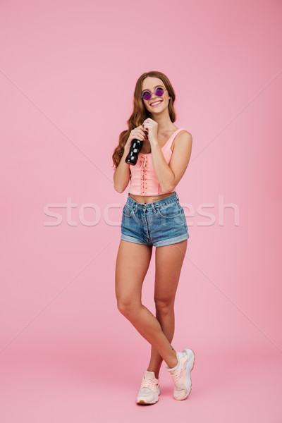 Full length portrait of young smiling beautiful girl in glasses  Stock photo © deandrobot