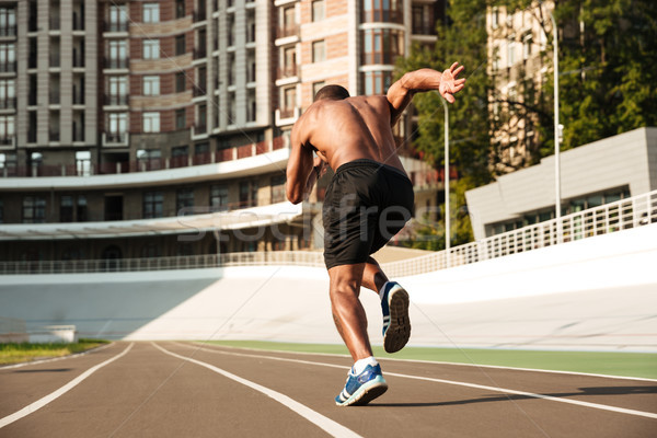Back view of afro american sprinter starting on the running trac Stock photo © deandrobot