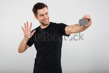 Portrait of a smiling young guy waving to camera Stock photo © deandrobot