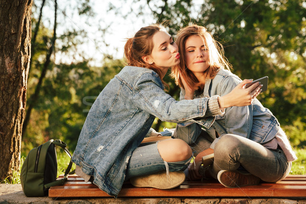 Two playful young woman in jeans wear making selfie while sittin Stock photo © deandrobot