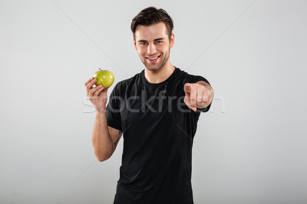 Smiling young sports man holding apple pointing at you. Stock photo © deandrobot