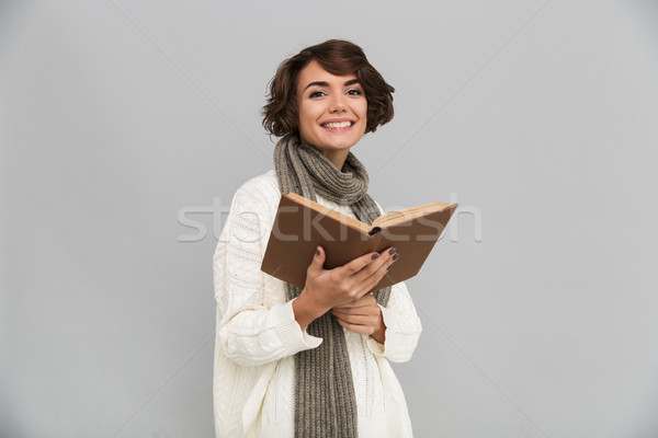 Smiling young pretty woman wearing scarf reading book. Stock photo © deandrobot
