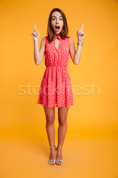 Full length portrait of pretty surprised woman in red dress poin Stock photo © deandrobot