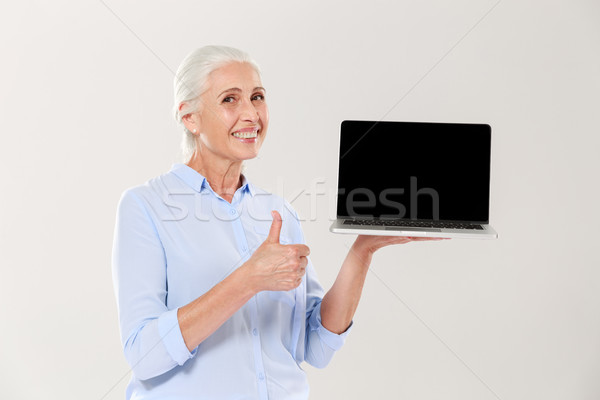 Old woman holding laptop and showing thumb up isolated Stock photo © deandrobot