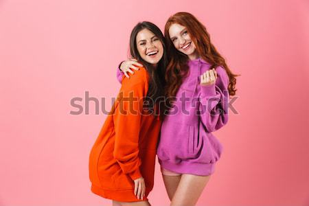 Two smiling women hugging and looking at the camera Stock photo © deandrobot
