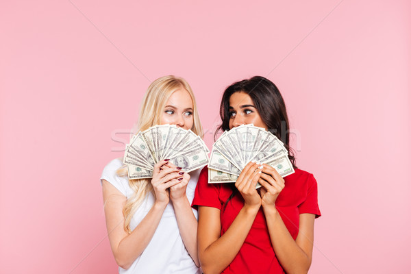 Two smiling women hiding behind the money Stock photo © deandrobot