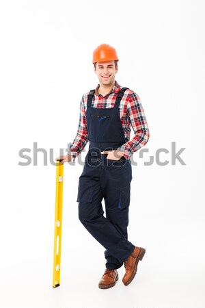 Full length portrait of a smiling young male builder Stock photo © deandrobot
