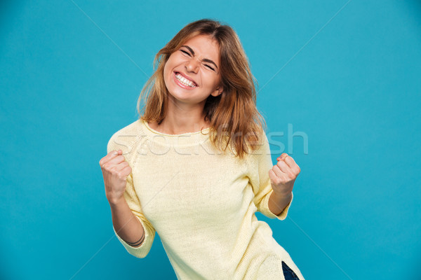 Happy young woman showing winner gesture. Stock photo © deandrobot
