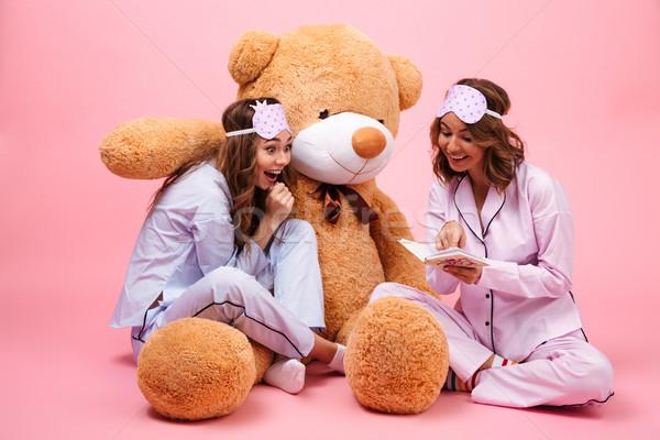 Kettő izgatott fiatal lányok pizsama ül Stock fotó © deandrobot