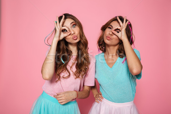 Two attractive woman in girls in children's clothes looking thro Stock photo © deandrobot