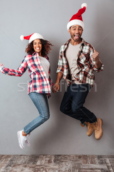 Full length portrait of a cheery happy african couple Stock photo © deandrobot