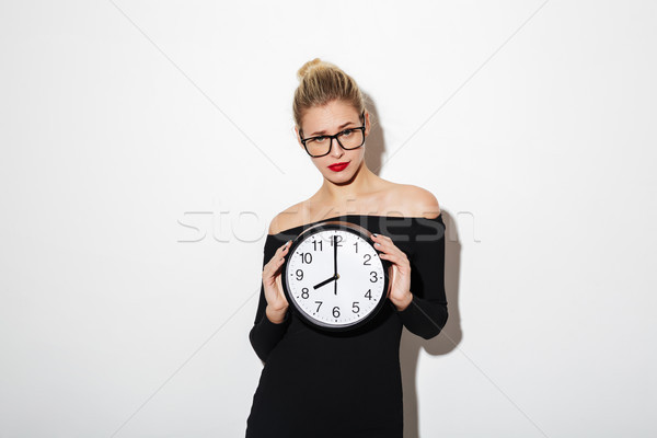 Confused business woman in dress and eyeglasses holding clock Stock photo © deandrobot