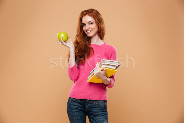 Portrait of a cheery pretty redhead girl holding apple Stock photo © deandrobot