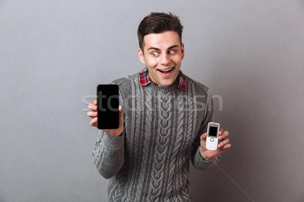 Intrigued man in sweater choosing between smartphones Stock photo © deandrobot