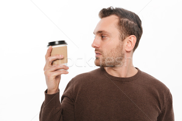 Young man drinking coffee. Looking aside. Stock photo © deandrobot