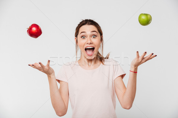 Portrait of a happy girl throwing apples in the air Stock photo © deandrobot