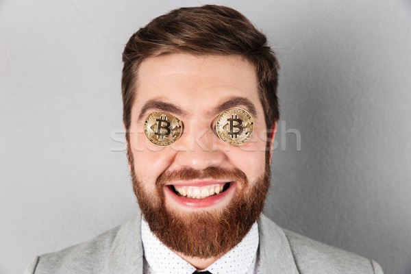 Close up of a happy businessman with bitcoins Stock photo © deandrobot