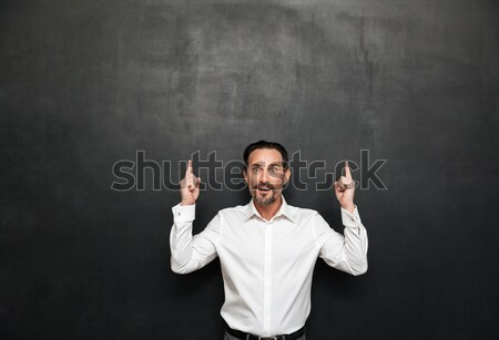 Portrait of brunette bearded man in white shirt touching his chi Stock photo © deandrobot