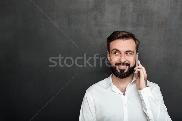 Happy man talking on mobile phone having pleasant conversation l Stock photo © deandrobot