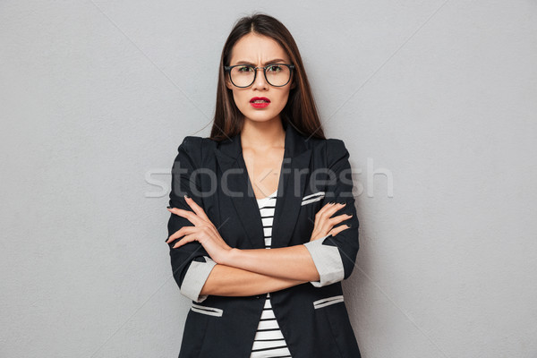 Serious asian business woman in eyeglasses with crossed arms Stock photo © deandrobot