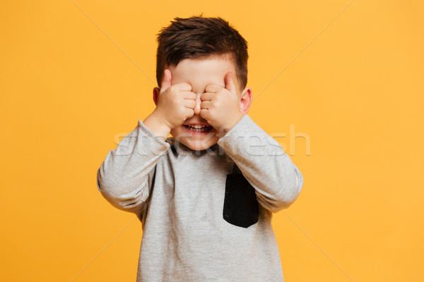 Smiling cute little boy child showing thumbs up covering eyes. Stock photo © deandrobot