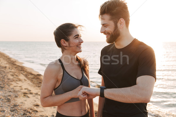 Smiling young sport couple showing smartwatch Stock photo © deandrobot