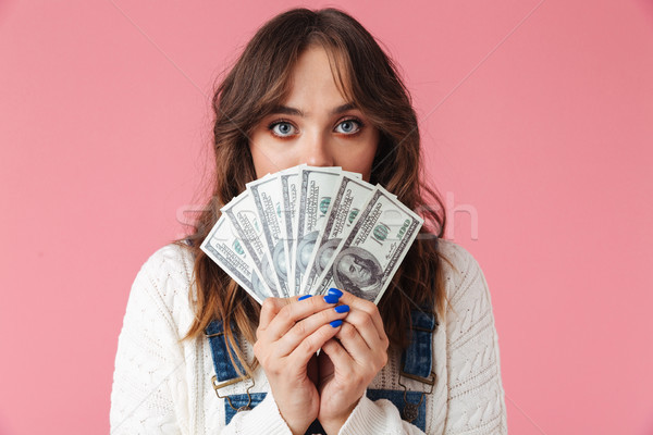 Portrait of a pretty young girl holding money Stock photo © deandrobot