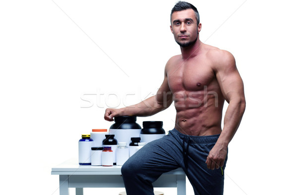 Handsome muscular man leaning on the table with sports nutrition Stock photo © deandrobot