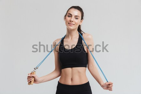 Young happy sport woman showing her biceps over white background Stock photo © deandrobot
