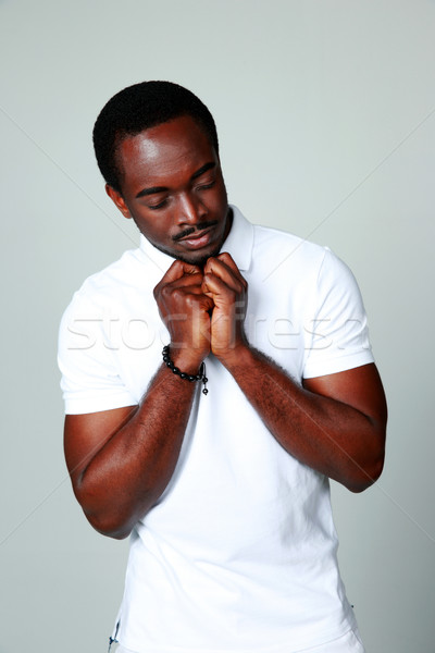 African man praying with his eyes closed on gray background Stock photo © deandrobot