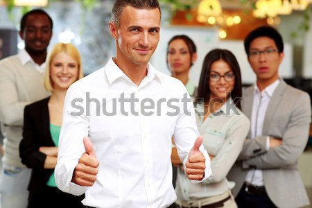 Group of business people giving thumb up to camera in the office Stock photo © deandrobot