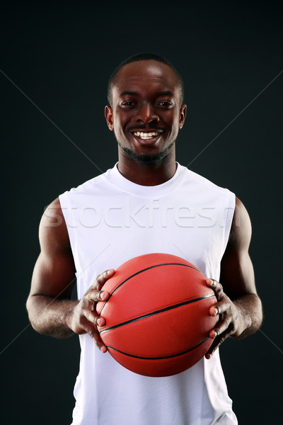 Smiling african american basketball player over black background Stock photo © deandrobot