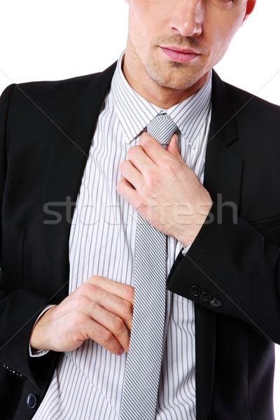 Businessman straightening his tie over white background Stock photo © deandrobot