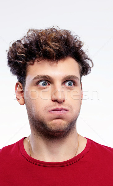 Funny young man inflate his cheeks over gray background Stock photo © deandrobot