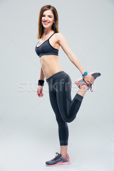 Stock photo: Happy sporty woman stretching leg